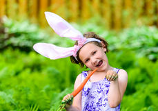 兔宝宝耳朵的女孩吃红萝卜的 免版税库存照片