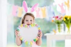 兔宝宝耳朵的小女孩在复活节彩蛋狩猎 图库摄影