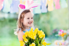 兔宝宝耳朵的小女孩在复活节彩蛋狩猎 库存照片