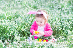 兔宝宝耳朵的小孩女孩用鸡蛋在春天开花 免版税库存图片