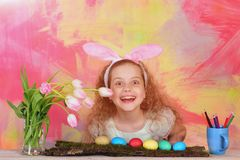 兔宝宝耳朵的愉快的复活节女孩有铅笔的,鸡蛋,花 免版税库存照片