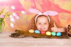 兔宝宝耳朵的愉快的复活节女孩用五颜六色的鸡蛋,花 库存图片