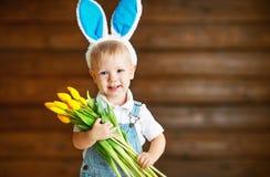 兔宝宝耳朵的愉快的笑的男婴有在wo的黄色郁金香的 免版税库存图片