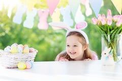 兔宝宝耳朵的滑稽的小女孩在早餐在复活节早晨在桌上用复活节彩蛋 库存照片