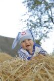 兔宝宝衣服的一个逗人喜爱的婴孩在秸杆说谎 免版税库存图片