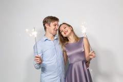 党、家庭和假日概念-拿着在白色背景的年轻夫妇闪烁发光物 库存图片