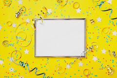 党、狂欢节或者生日背景装饰了与五颜六色的五彩纸屑的银色在黄色台式视图的框架和飘带 免版税库存图片