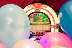 党五颜六色的气球和自动电唱机背景 库存照片