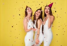 党和假日概念 豪华闪烁衣服饰物之小金属片的三名魅力妇女穿戴跳舞和获得与五彩纸屑的乐趣和 免版税库存图片