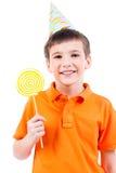 党帽子的微笑的男孩用色的糖果 免版税库存照片