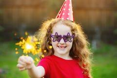 党帽子的愉快的女孩有灼烧的闪烁发光物的在她的手上 免版税库存图片