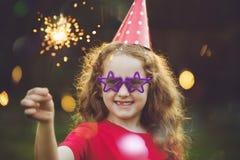党帽子的愉快的女孩有灼烧的闪烁发光物的 图库摄影