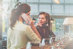 党,业务会议 两个年轻女商人是与玻璃的常设近的酒吧柜台和谈话在手机 图库摄影