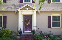 入口和beauitufl与紫色快门的被绘的砖和木瓦村庄的前门和triming和花圈和玫瑰和p 免版税库存图片