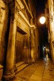 从入口的夜狭窄的欧洲街道到relizioznoe大厦在希贝尼克,克罗地亚的历史的中心 免版税库存照片