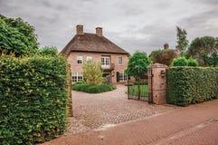 入口门开放对庭院庭院在典雅的砖房子里在一多云天在Drimmelen 免版税图库摄影
