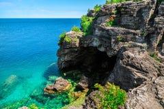 入口令人惊讶的邀请的看法对洞穴的从湖在布鲁斯半岛Cyprus湖,安大略支持 免版税库存照片