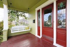 入在红色和绿色的门廊与垂悬的摇摆 免版税图库摄影