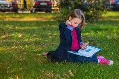 入学年龄的一个美丽的女孩的画象在秋天公园 免版税库存图片