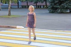 入学年龄的女孩穿过在一条行人交叉路的路 库存照片