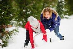 入学年龄的少妇和女孩修造雪人 库存图片