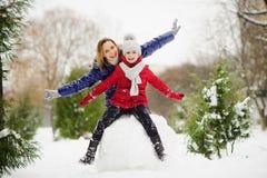 入学年龄的少妇和女孩修造雪人 免版税图库摄影
