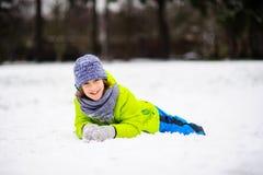 入学年龄的男孩在明亮的冬天总体的在雪说谎 图库摄影