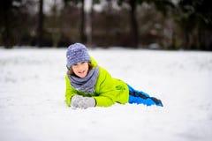 入学年龄的男孩在明亮的冬天总体的在雪说谎 库存照片