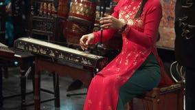 全国礼服的亚裔妇女在她的国家,民间音乐,有助合奏的一台串民间仪器使用 影视素材