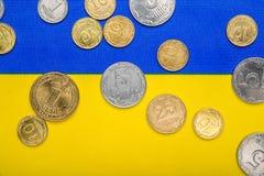 以全国黄色蓝色旗子为背景的乌克兰全国硬币 欧洲电视网货币 库存图片