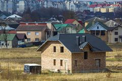 全新的宽敞有瓦屋顶和窗口开头的砖二层的住宅房子在背景的郊区邻里 免版税库存图片