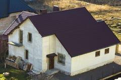 全新的宽敞砖涂了灰泥有棕色等待它的所有者的瓦屋顶和窗口的二层的住宅家庭房子 Bu 免版税库存图片