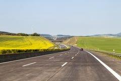 全新的高速公路路在德国 在绿色领域之间的机动车路 免版税库存照片