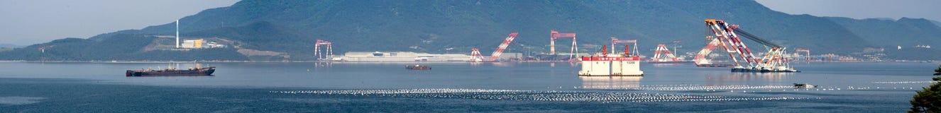 全景下面被修建岸平台和起重机闯入在海湾的船锚在三星重工业或石牌前面 免版税库存图片