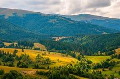 全景与蓝色多云天空的喀尔巴阡山脉风景在夏天 库存图片