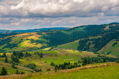 全景与蓝色多云天空的喀尔巴阡山脉风景在夏天 免版税库存图片