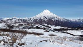 全景冬天多山风景:火山多雪的锥体  免版税图库摄影