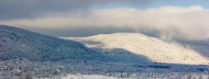 全景冬天风景、一个村庄多雪的小山山麓小丘的和朝阳的第一光芒 图库摄影