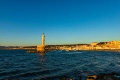 全景威尼斯式港口江边和灯塔在干尼亚州,克利特,希腊老港口日落的 免版税库存图片