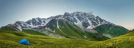 全景山环境美化与在旅游阵营的帐篷在象草的山谷 E 迁徙在狂放的自然 库存照片