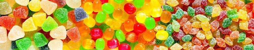 全景接近从糖罐头五颜六色的甜点的背景  免版税库存照片