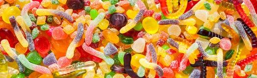 全景接近从糖罐头五颜六色的甜点的背景  库存图片
