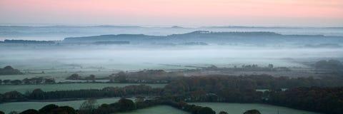 全景有薄雾的乡下风景充满活力的黎明日出 免版税库存照片