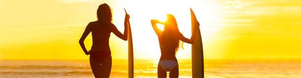 全景比基尼泳装冲浪者妇女女孩冲浪板日落海滩 库存照片