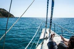 全景海洋和风景在有女孩的意大利撒丁岛射击了游艇的前面在夏时的 图库摄影