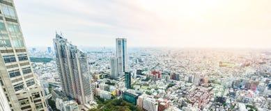 全景现代在剧烈的太阳和早晨蓝色多云天空下的城市地平线鸟眼睛鸟瞰图在东京,日本 免版税库存图片