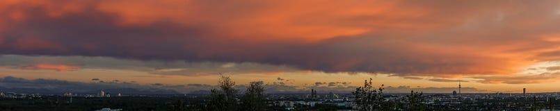 全景被采取在慕尼黑市的日落在巴伐利亚,有剧烈的多云天空和山的德国在背景中 库存照片