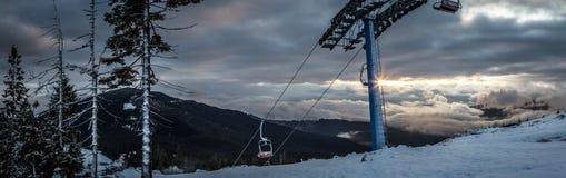 全景雪与滑雪电缆车的山风景 在喀尔巴阡山脉的日出在乌克兰 库存图片