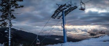 全景雪与滑雪电缆车的山风景 在喀尔巴阡山脉的日出在乌克兰 库存照片