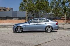全景BMW 320D蓝色 都市的场面 库存图片